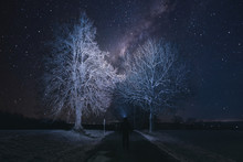 Silhouette Of Hiker Person With Flashlight On Head Watching The Starry Sky And Tree On The Road