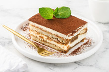 Traditional Italian Dessert Tiramisu On A White Plate On A Marble Table. Close-up. Selective Focus