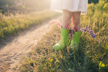 Creative Bouquet Of Flowers In Green Boots On The Green Grass.