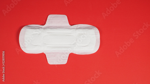 Photo Sanitary napkin top angle view  on red background.