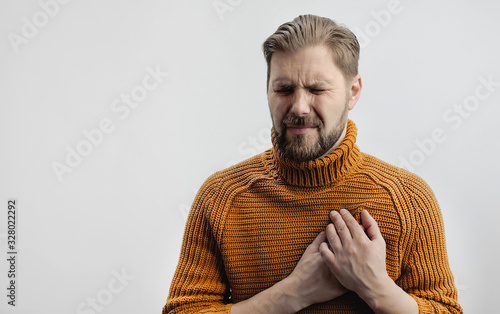 Photo Portrait of grimacing bearded man placing hands on chest suffering from heartach