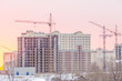winter day, the construction of multi-story frame houses with tower cranes, the demolition of old houses, in a light key