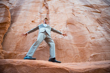 Nervous Businessman Balancing On A Narrow Ledge In A Red Rock Canyon