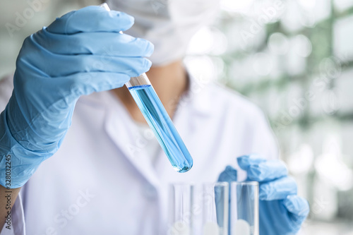 Fotomural Scientist or medical in lab coat holding test tube with reagent, Laboratory glas