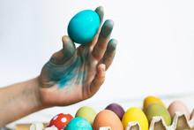 Blue Easter Egg In Hand On White Background. Painting Easter Eggs