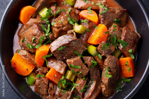 Fototapeta Beef meat and vegetables stew in black bowl. Dark background. Close up. obraz