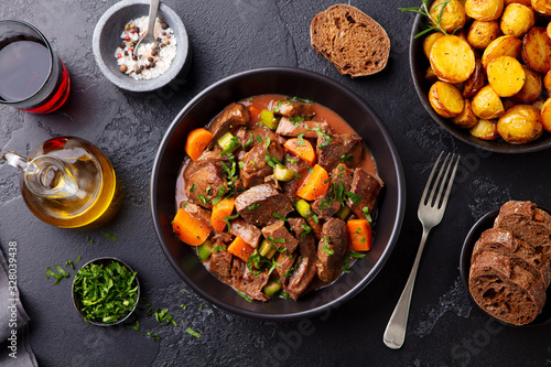 Fototapeta Beef meat and vegetables stew in black bowl with roasted baby potatoes. Dark background. Top view. obraz