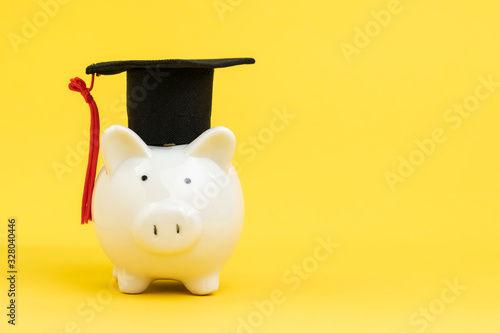 Foto White piggy bank wearing graduation cap on yellow background with copy space, ed