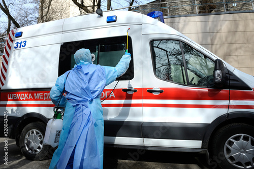 Paramedics disinfecting the ambulance car with the motorized backpack atomizer a Canvas Print