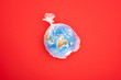 Top view of globe in plastic bag isolated on red, global warming concept