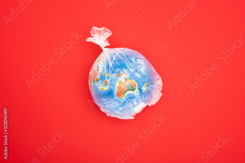 Top view of globe in plastic bag isolated on red, global warming concept Canvas Print