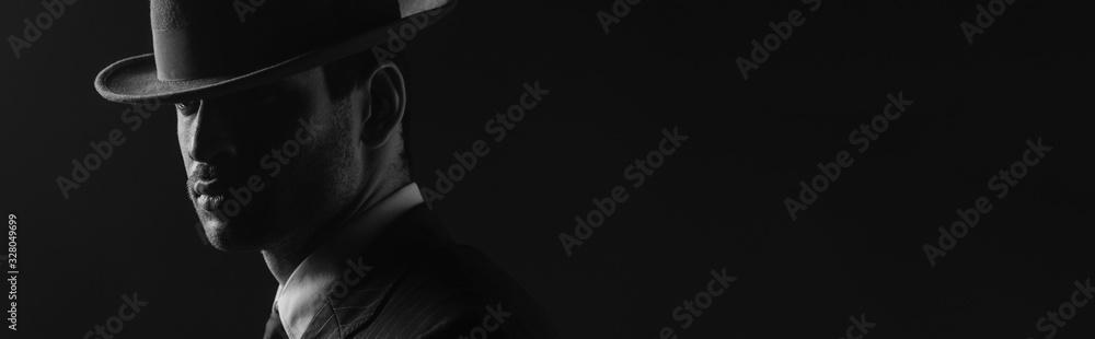 Fototapeta Monochrome image of mafioso with felt hat isolated on black, panoramic shot