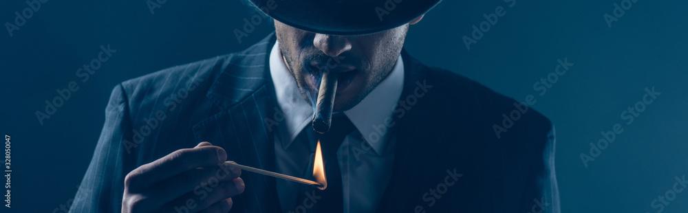 Fototapeta Mafioso lighting cigar with match on dark blue, panoramic shot