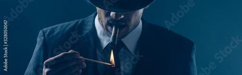 Fototapeta Mafioso lighting cigar with match on dark blue, panoramic shot obraz