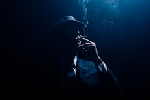 Silhouette Of Mafioso In Suit And Felt Hat Smoking Cigarette On Dark Blue Background
