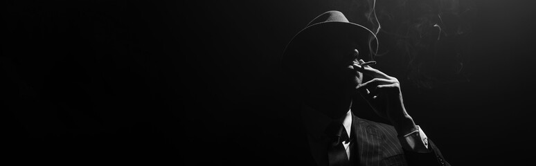 Monochrome image of mafioso silhouette smoking on black background, panoramic...