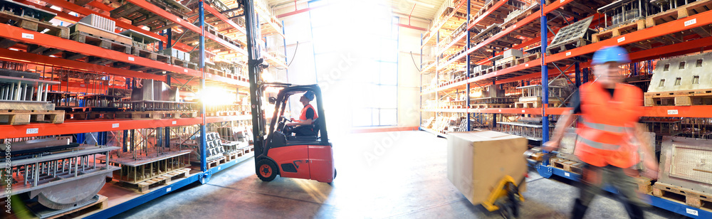Fototapeta logistics and transport workers in a goods warehouse with goods for storage and shipping