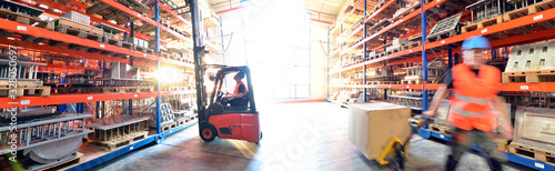 Fototapeta logistics and transport workers in a goods warehouse with goods for storage and shipping obraz