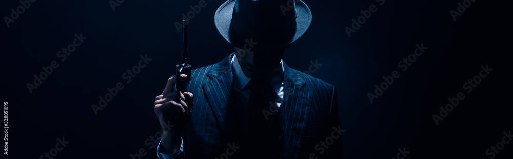 Fototapeta Silhouette of gangster raising gun on dark blue background, panoramic shot