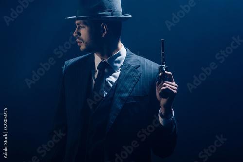 Fototapeta Gangster raising revolver and looking away on dark background