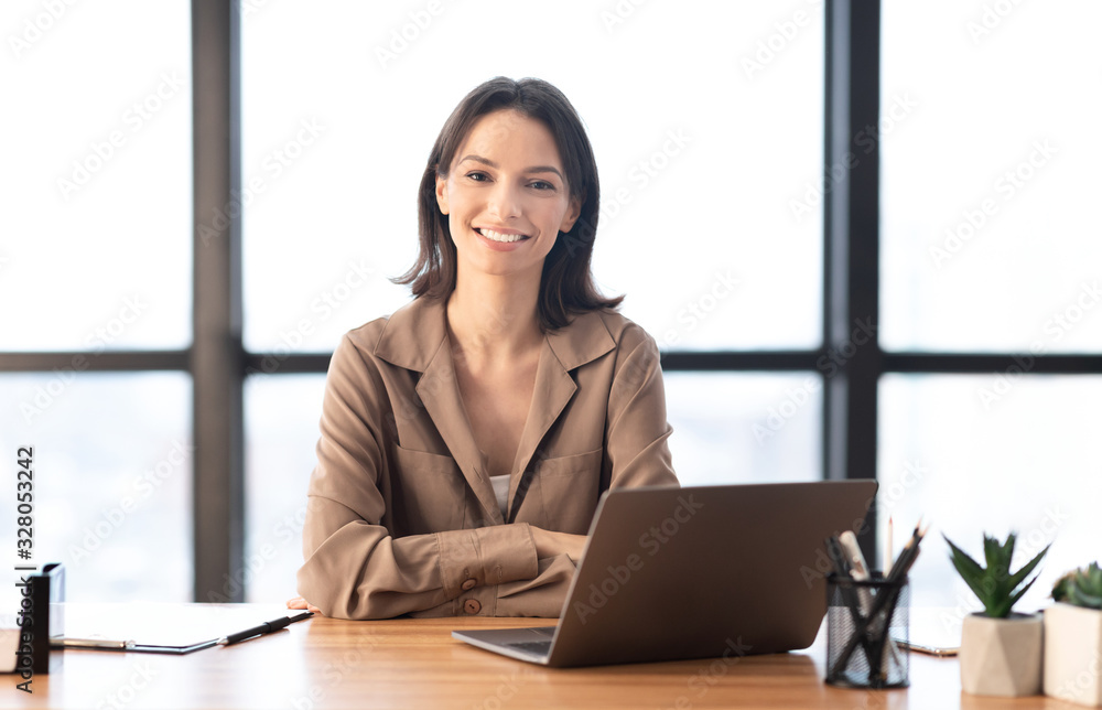 Fototapeta Young manager smiling at camera in contemporary office