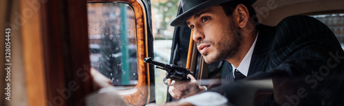 Selective focus of gangster sitting in ambush with gun in retro car, panoramic s Wallpaper Mural