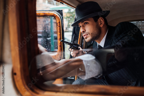Selective focus of gangster sitting in ambush with gun in retro car Wallpaper Mural