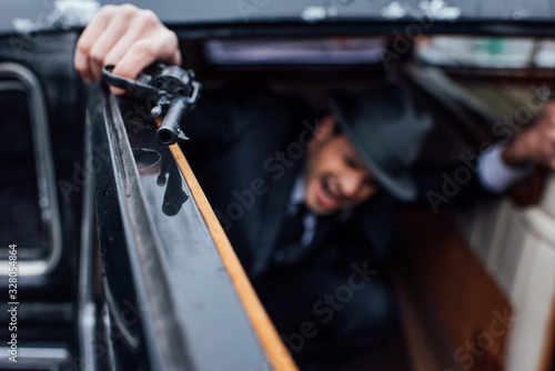 Photo Selective focus of gangster sitting in ambush with revolver in car
