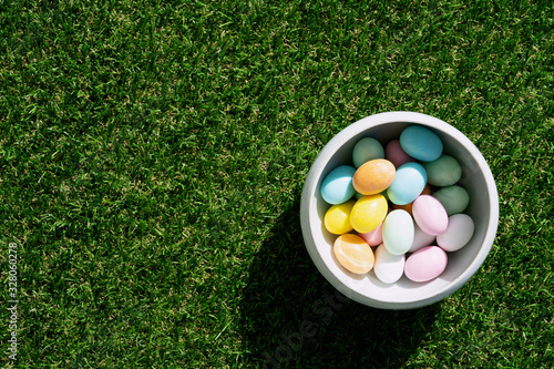 Fototapeta Chocolate Easter eggs glazed with pastel coloring in a bowl over green grass background. Happy Easter concept. Copy space. Top view obraz