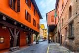 Fototapeta Uliczki - Old narrow street in Bologna, Emilia Romagna, Italy. Architecture and landmark of Bologna. Cozy cityscape of Bologna.