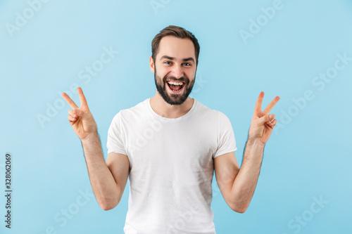 Obraz Portrait of a young cheerful bearded man wearing t-shirt - fototapety do salonu