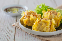 Chinese Steamed Dumpling, Shumai On White Dish Served With Soy Sauce And .lettuce Leaves On Brown Cloth And Wooden Table. Delicious Dimsum Pork.