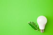White Led Light Bulb And Leaf On Bright Green Table Background. Closeup. Energy Saving. Empty Place For Text Or Logo. Top Down View.