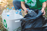 A woman picking up garbage plastic bottles into a box and plastic bag for recycling concept