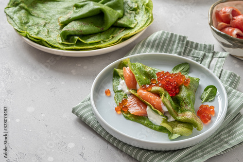 Fototapeta Green spinach crepes with smoked salmon, red caviar and yogurt sauce obraz