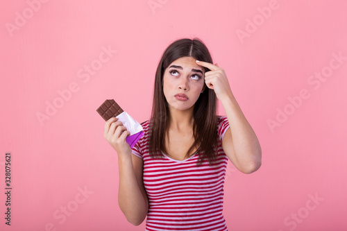 Teenage girl with acne problem holding chocolate bar against pink background Wallpaper Mural