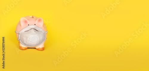 Cuadros en Lienzo Piggy bank wearing mask on yellow background