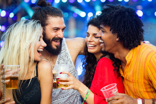Group of happy friends hanging out and enjoying drinks, festival