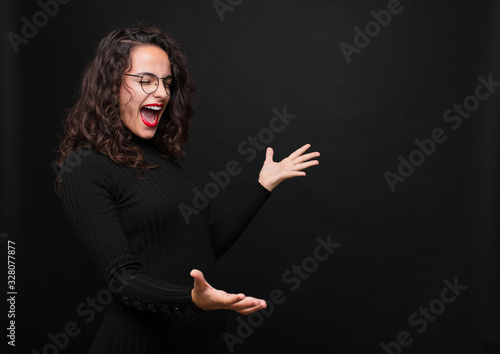 Fototapeta young pretty woman performing opera or singing at a concert or show, feeling romantic, artistic and passionate against black background