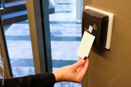Obraz Women hand reaching to use RFID key card to access to office building area and workspace. In building security only for authorized person - fototapety do salonu