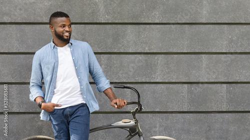 Fototapeta Handsome black man standing with bike against urban wall, looking away obraz