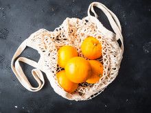 Frische Orangen In Einer Einkaufstasche Aus Netz, Nachhaltige Lebensweise, Draufsicht, Rustikaler Hintergrund, Umweltschutz, Eco