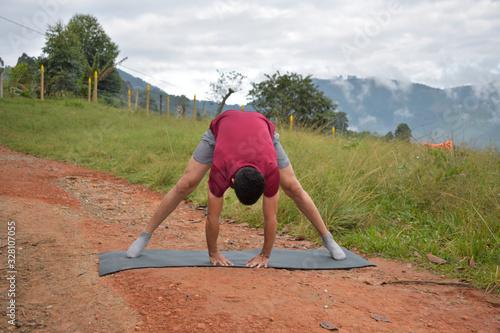 Joven latino haciendo ejercicios en una montaña Wallpaper Mural