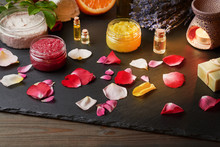 Jar Scrub And Aromatherapy Essential Oil Stand On A Dark Stone Board. Around Rose Petals, A Bouquet Of Lavender, Orange, Rosehip, Homemade Soap And A Lamp For Aromatherapy