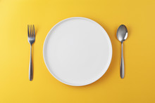 Empty White Plate With Spoon And Fork On Yellow Background
