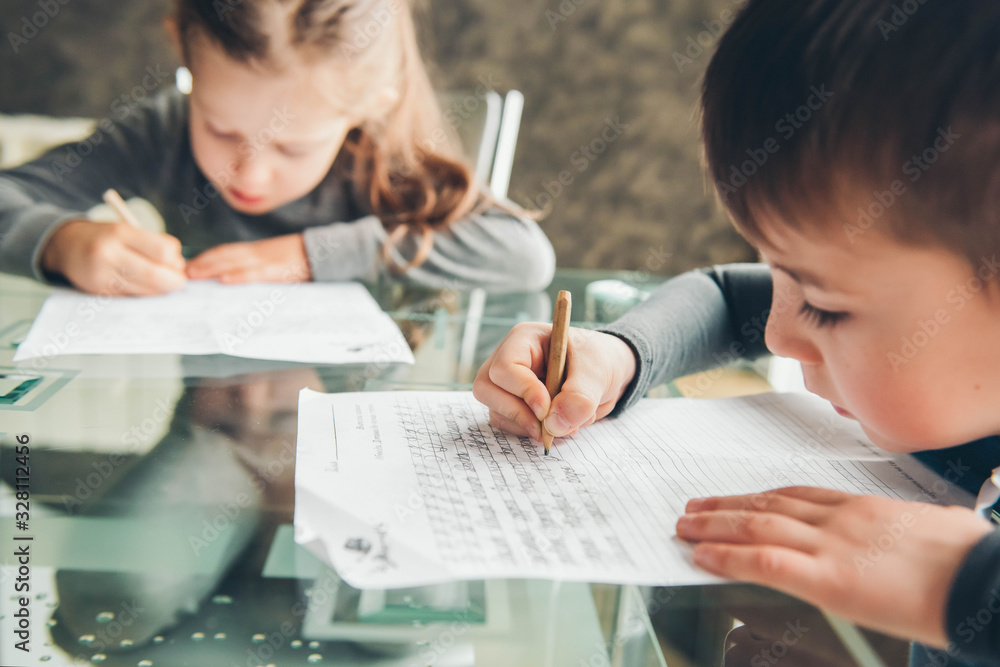 Fototapeta Schoolboy and schoolgirl writing letters. Close-up  pencil in the hand of child. Children learning to write letters at the table.