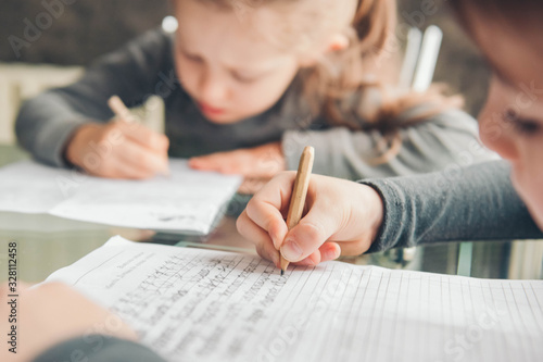 Fototapeta Schoolboy and schoolgirl writing letters. Close-up  pencil in the hand of child. Children learning to write letters at the table. obraz