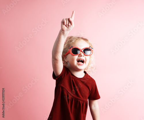 фотография Insight: a little girl a preschool girl in sunglasses exclaims and raises a finger up
