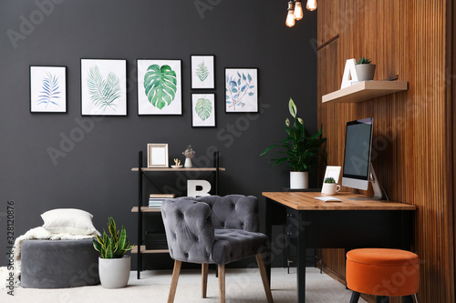 Comfortable workplace with computer near wooden wall in stylish room interior Slika na platnu