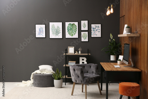 Obraz Comfortable workplace with computer near wooden wall in stylish room interior. Home office design - fototapety do salonu